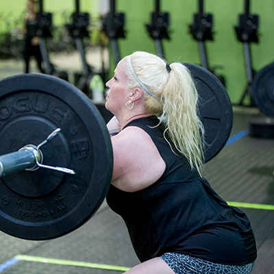 Woman cleans weight at CrossFit Iron Refined class in Eagle River Alaska.
