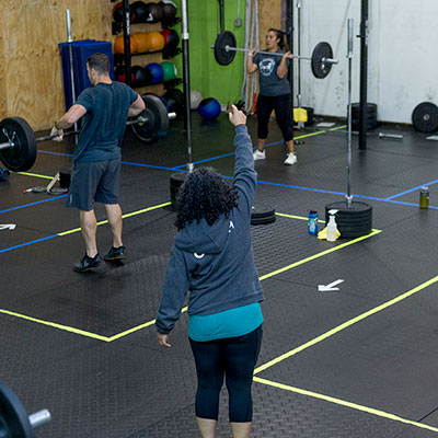 Coach Erika leads CrossFit Iron Refined class in Eagle River Alaska with socially distanced boxes.