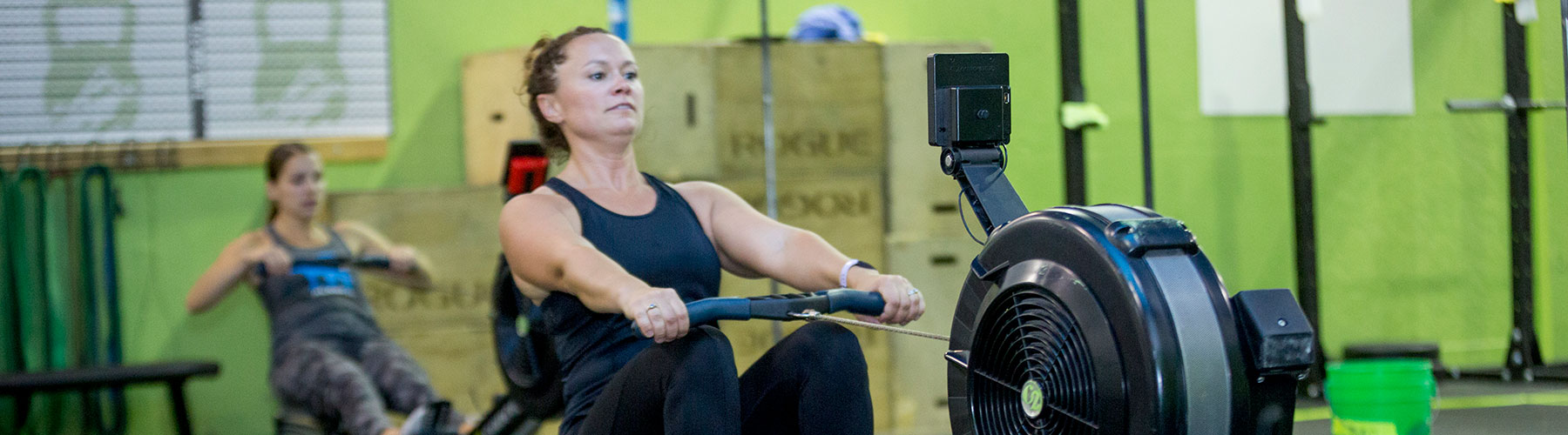 Woman rowing at CrossFit Iron Refined in Eagle River Alaska.